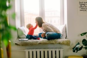 Mother and toddler sitting in front of a window and playing